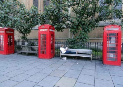UK---London---Reading-a-book-by-Red-Telephone-Booths